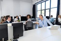 Офис открытого пространства концепции команды дела работая современный, сотрудники группы предпринимателей сидя на компьютерах го Стоковое Изображение RF