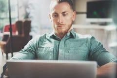 Офис просторной квартиры дизайна интерьера компьтер-книжки бородатого бизнесмена работая современный Человек сидя винтажный стул  Стоковые Фотографии RF