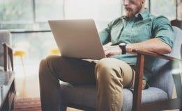 Офис просторной квартиры дизайна интерьера компьтер-книжки стильного бизнесмена работая современный Человек сидя винтажный стул И Стоковые Фотографии RF