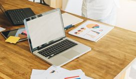 Офис, стол Конец-вверх компьтер-книжки на деревянном столе Рядом бумажные графики, диаграммы, диаграммы, цифровая таблетка Стоковые Изображения RF