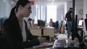 Офис, утомленная девушка дела с стеклами использует устройство и думает о что-то пока работающ крупный план акции видеоматериалы