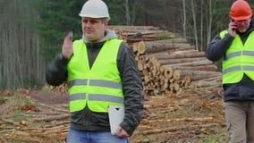 Офицеры леса говоря на сотовых телефонах в лесе сток-видео