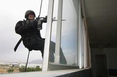 Офицер команды СВАТ Rappelling и направляя оружие Стоковые Изображения RF