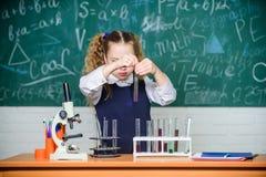 Официальное образование Будущая лаборатория школы микробиолога Эксперимент по школы проведения студента девушки умный Зрачок школ стоковое фото rf