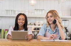 Официантка говоря на smartphone пока коллега используя цифровую таблетку Стоковые Фото