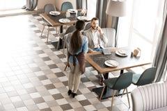 Официантка ждать пока клиент говоря на телефоне стоковая фотография