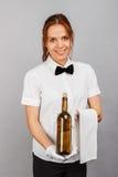 Официантка женщины с бутылкой вина, серой предпосылки Стоковые Изображения RF