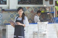 Официантка используя цифровую таблетку в кафе Стоковое Фото
