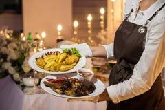 Официантка носит 2 плиты с мясным блюдом стоковые фотографии rf