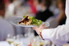 Официантка нося плиту с тарелкой мяса Стоковое Изображение RF