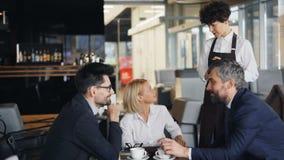 Официантка принимая заказ от группы в составе люди и дама предпринимателей говоря на таблице видеоматериал
