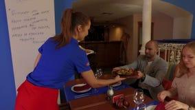 Официантка приносит гостям горячие вкусные блюда видеоматериал