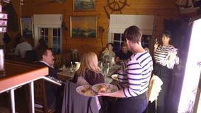 Официантка приносит законченное блюдо от кухни в залу сток-видео
