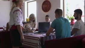 Официантка приносит пить к компании людей изучая в кафе акции видеоматериалы