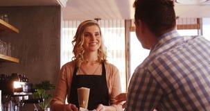 Официантка служа стекло холодного кофе к клиенту акции видеоматериалы
