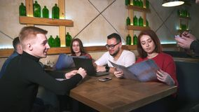 Официант в ресторане принимает заказ от группы в составе друзья акции видеоматериалы