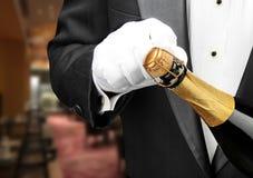 Официант в ресторане раскрывая бутылку шампанского стоковое изображение rf
