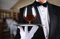 Официант в ресторане с snifter рябиновки на служа подносе стоковое фото rf