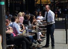 Официант и туристы в Париже, Франции стоковые фотографии rf