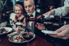 Официант льет вино и бизнесмен останавливает его стоковая фотография