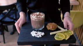 Официант носит заказ к какао клиента с зефиром в стекле утеса, который служат на деревянном черном подносе с тортом и акции видеоматериалы