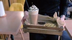 Официант носит заказ к клиенту ирландский кофе служил с вафлями на подносе r акции видеоматериалы