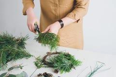 Оформитель флориста делая венок рождества Стоковое Фото