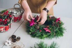 Оформитель флориста делая венок рождества Стоковое фото RF