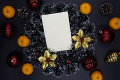 Оформление и tangerines ели венка, красного цвета и золота рождества на черной предпосылке Пустая карта с местом текста стоковая фотография rf