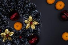 Оформление и tangerines ели рождества на черной предпосылке Состав венка сезона зимнего отдыха стоковое изображение