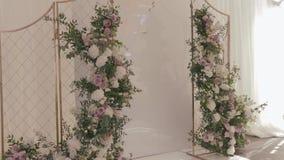 Оформление свадьбы ресторана Алтар золотой свадьбы украшенный с garlends стоек растительности и белых роз в сток-видео
