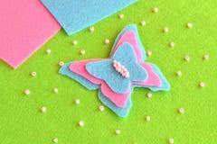 Оформление бабочки зашитое от войлока пинка и сини Весна или идея лета простая DIY для детей Стоковые Фотографии RF