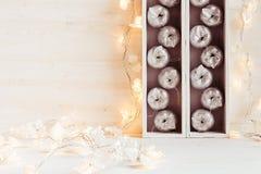 Оформление рождества мягкое домашнее серебряных яблок и светов горя в коробках на деревянной белой предпосылке Стоковое Изображение RF