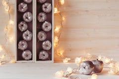 Оформление рождества мягкое домашнее серебряных яблок и светов горя в коробках на деревянной белой предпосылке Стоковая Фотография