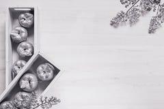 Оформление рождества серебряных яблок в коробках на деревянной белой предпосылке Стоковая Фотография