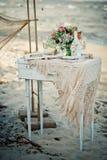 Оформление свадьбы с бутылкой, стеклами, цветками, cockleshells моря Стоковая Фотография