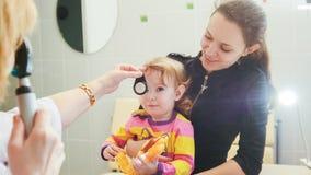 Офтальмология - доктор проверяет зрение на маленькой девочке - здравоохранение ` s ребенка Стоковые Фотографии RF
