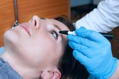 Офтальмолог выполняет деятельность для того чтобы диагностировать зрение маленькой девочки Стоковые Фотографии RF