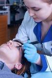 Офтальмолог выполняет деятельность для того чтобы диагностировать зрение маленькой девочки Стоковая Фотография