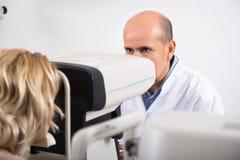 Офтальмолог проверяя зрение на женском пенсионере Стоковое Фото