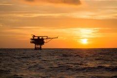 Оффшорное масло и платформа снаряжения во времени захода солнца или восхода солнца Конструкция производственного процесса в море  Стоковые Фото