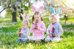 Охота пасхального яйца сада Дети едят шоколад зайчика Стоковая Фотография