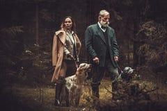 2 охотника с собаками и корокоствольными оружиями в традиционной одежде стрельбы, представляя на темной предпосылке леса Стоковое Фото