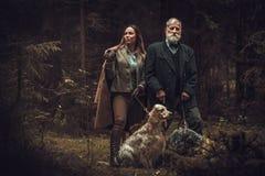 2 охотника с собаками и корокоствольными оружиями в традиционной одежде стрельбы, представляя на темной предпосылке леса Стоковое Изображение RF