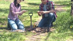 Охотники за сокровищами девушки и человека выкапывая вверх старые монетки нашли в парке с металлоискателем сток-видео