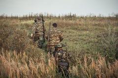 Охотники идя вверх через сельское поле во время сезона звероловства стоковое изображение