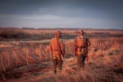 Охотники охотясь сельский восход солнца поля Поле покрашенное с оранжевым цветом восходящего солнца Стоковые Фотографии RF