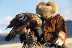 Охотник беркута, пока охотящся к зайцам держащ беркутов на его оружиях в горе пустыни западной Монголии Стоковые Изображения RF
