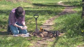 Охотник за сокровищами девушки вытягивает вне старую монетку найденную в поле с металлоискателем видеоматериал