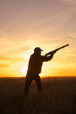 Охотник с корокоствольным оружием вверх в заходе солнца Стоковые Изображения
